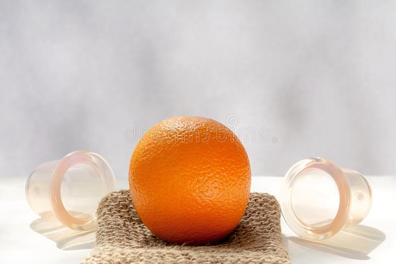 Die orange L?gen auf einem Maschenwaschlappen, der von den Naturfasern und nahe bei ihm gemacht wird, sind Vakuumbanken stockfotografie