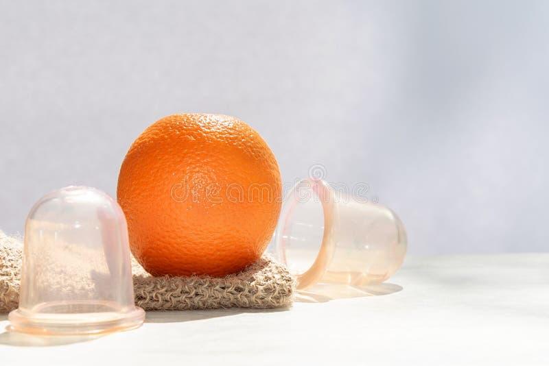 Die orange L?gen auf einem Maschenwaschlappen, der von den Naturfasern und nahe bei ihm gemacht wird, sind Vakuumbanken lizenzfreies stockbild