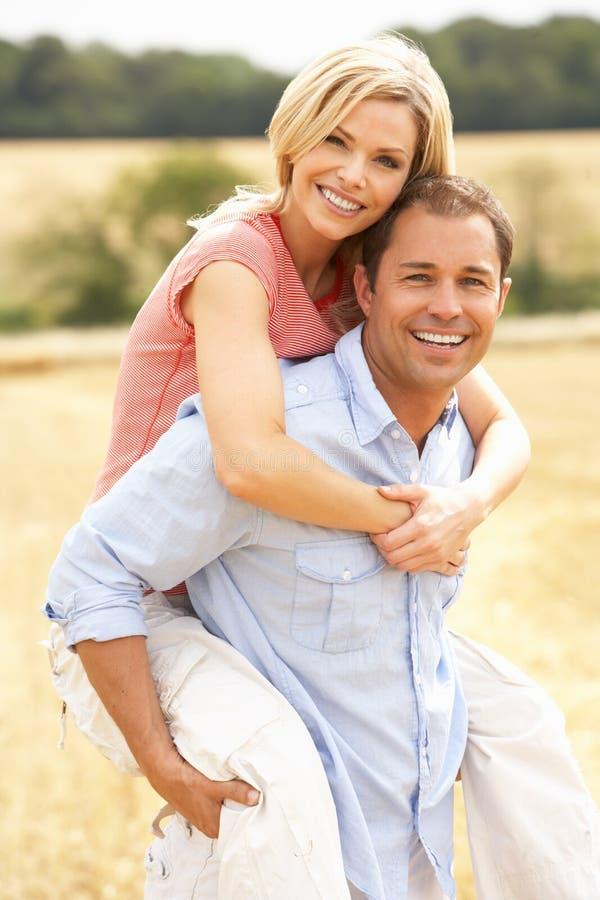 Die Paare, die Doppelpol im Sommer haben, ernteten Feld lizenzfreies stockbild