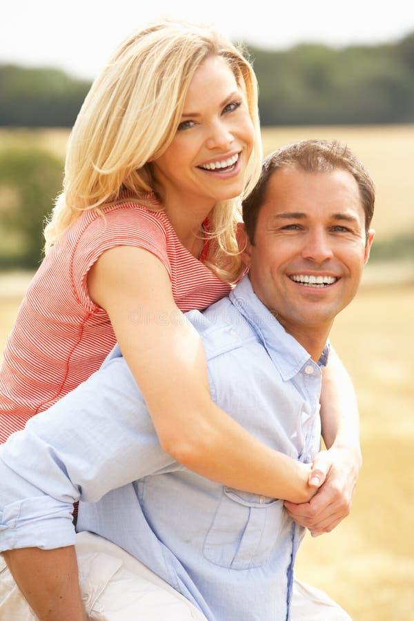 Die Paare, die Doppelpol im Sommer haben, ernteten Feld lizenzfreies stockfoto