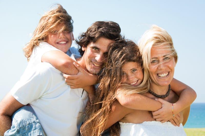 Die Paare, die Kinder geben, tragen Fahrdas lächeln huckepack lizenzfreie stockfotos