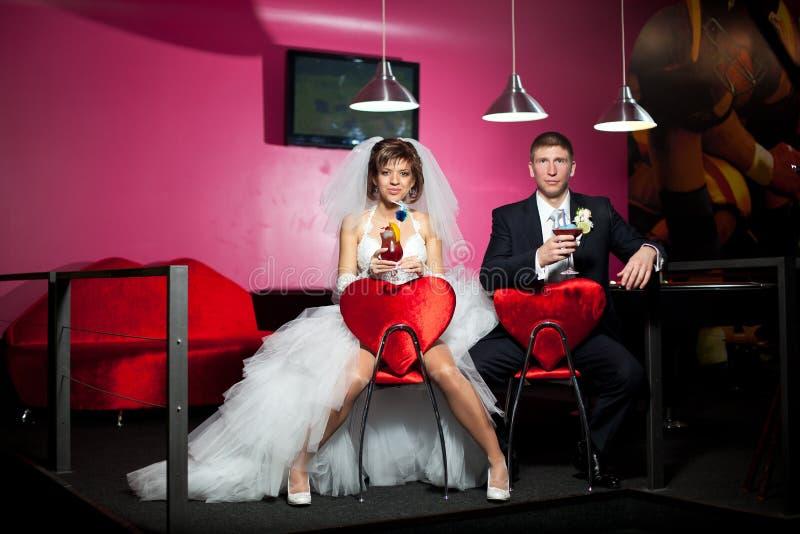 die Paare im Hochzeitstag, der in den Rotstühlen mit dem Herzen im Billardraum- und -getränkcocktail sitzt lizenzfreies stockfoto