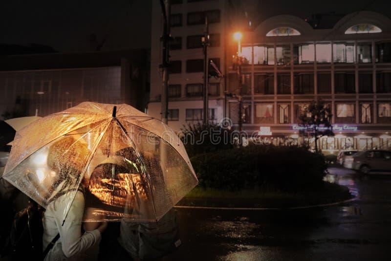 Die Paare küssen unter dem transparenten Regenschirm in der Nachtstraße beim Warten auf die Straßenrandverkehrsschilder am Eingan stockbild