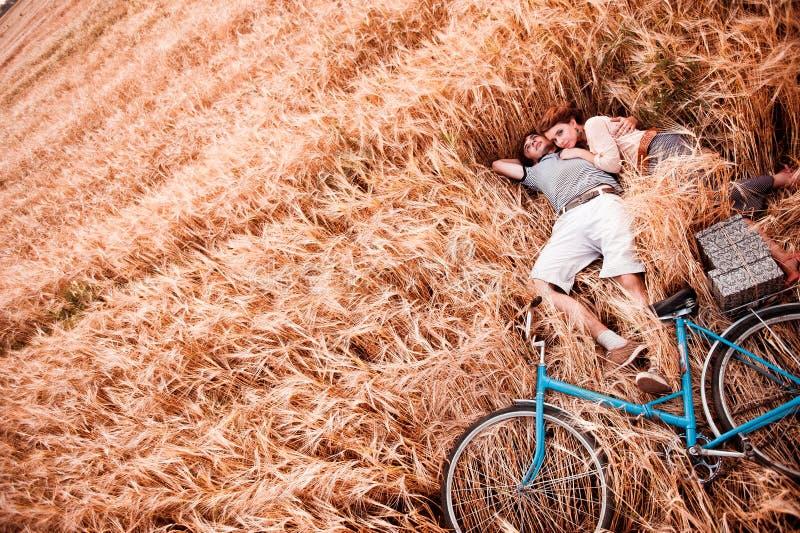 Die Paare - Mann, Mädchen und Fahrrad liegt auf dem Roggenfeld stockbild