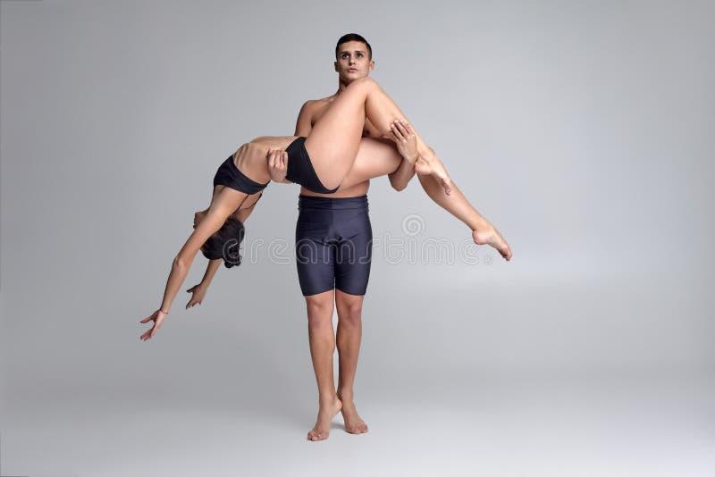Die Paare von T?nzern eines jungen modernen Balletts in den schwarzen Anz?gen werfen ?ber einem grauen Studiohintergrund auf lizenzfreies stockfoto