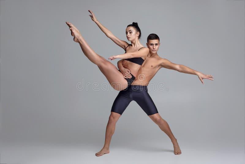 Die Paare von T?nzern eines jungen modernen Balletts in den schwarzen Anz?gen werfen ?ber einem grauen Studiohintergrund auf lizenzfreies stockbild