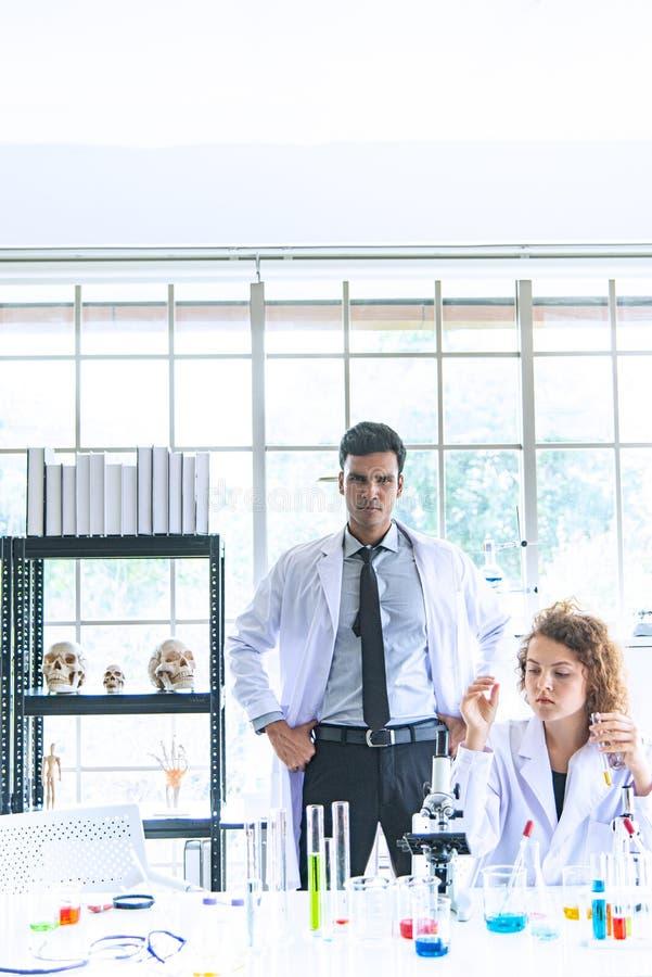 Die Paarreserchers, -wissenschaftler, -techniker, -zahnärzte oder -studenten, die Forschung oder Experiment oder bestimmen leiten stockfotografie