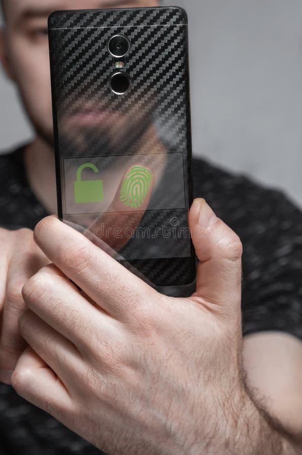 Die Person scannt den Fingerabdruck auf dem Telefonschirm, um auf das System zuzugreifen stockbild