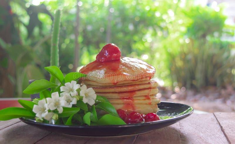 Die Pfannkuchen, die mit Erdbeersoßenbelag selbst gemacht sind, dienten mit frischen weißen Blumen auf Schwarzblech auf dem Tisch stockbilder