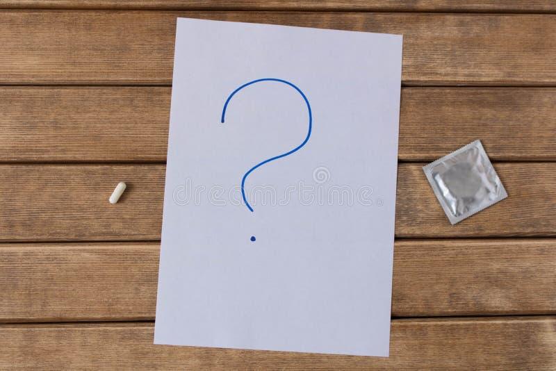 Die Pille und ein Kondom Auf dem Hintergrund des Holztischs lizenzfreie stockbilder