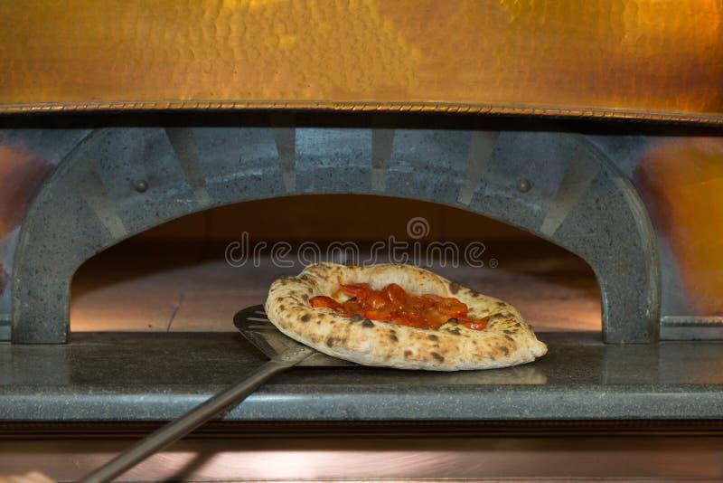 Die Pizza angefüllt mit Tomaten-Käse in elektrischen Ofen setzen stockfoto