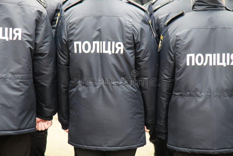 Die Polizisten in der Uniform mit der Aufschrift Polizei auf Ukrainisch, stehen die Straße in Dnipro-Stadt lizenzfreie stockbilder