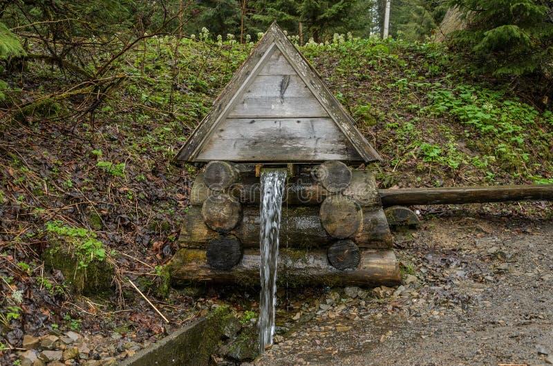 Die Quelle des Trinkwassers in den Bergen, unter dem Wald in Form eines Holzhauses stockfotografie