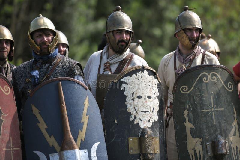 Die römischen Legionäre, die Sturzhelme und Schilder tragen, schauen an in der Verteidigungsbildung stockbilder
