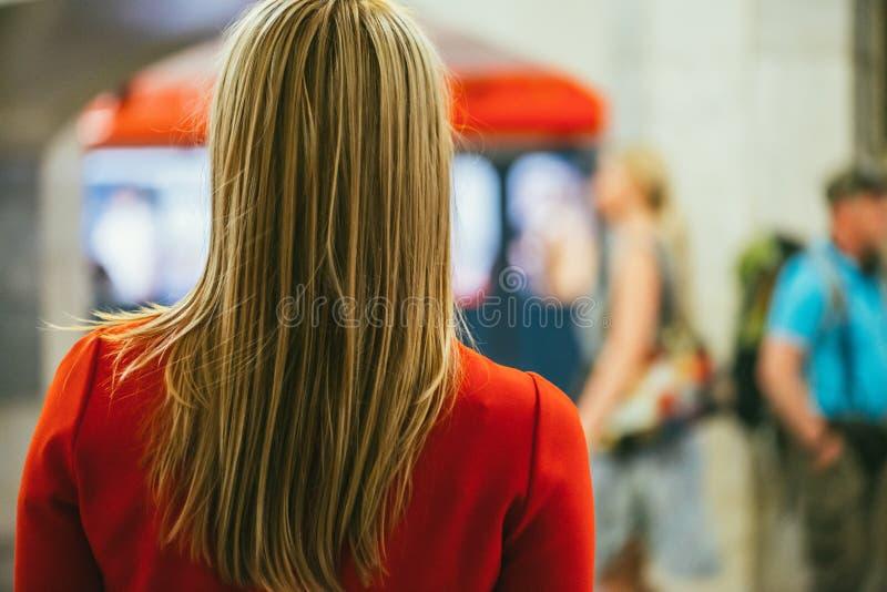 Die Rückseite über der Schulteransicht des schönen jungen Mädchens in einem roten Kleid gegen den unscharfen Hintergrund eines Un lizenzfreie abbildung