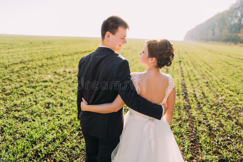 Die Rückseite der umarmenden und lächelnden Jungvermählten, die ihre Zeit auf dem Gebiet verbringen lizenzfreie stockbilder