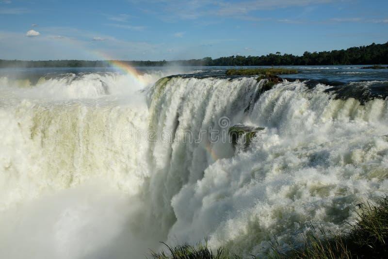 Die rasenden Iguaçu-Wasserfälle, Argentinien unter Regenbogen lizenzfreie stockfotografie