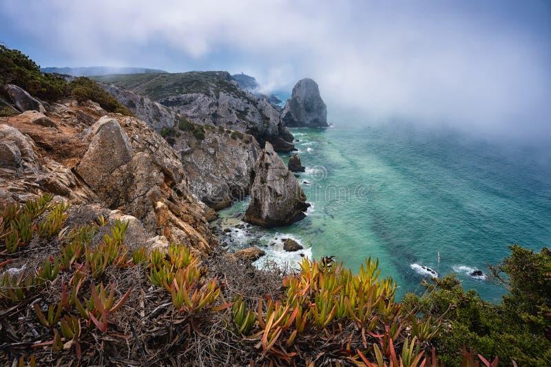 Die raue Küste am Atlantik mit Nebel, Blattwerk und Cabo da Roca Leuchtturm im Hintergrund in Sintra lizenzfreie stockfotografie