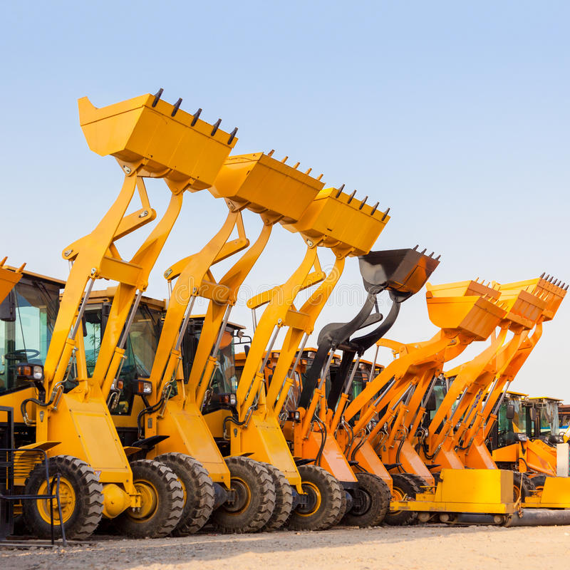 Die Reihe der Baggermaschine des schweren Baus gegen blaue SK stockfotos
