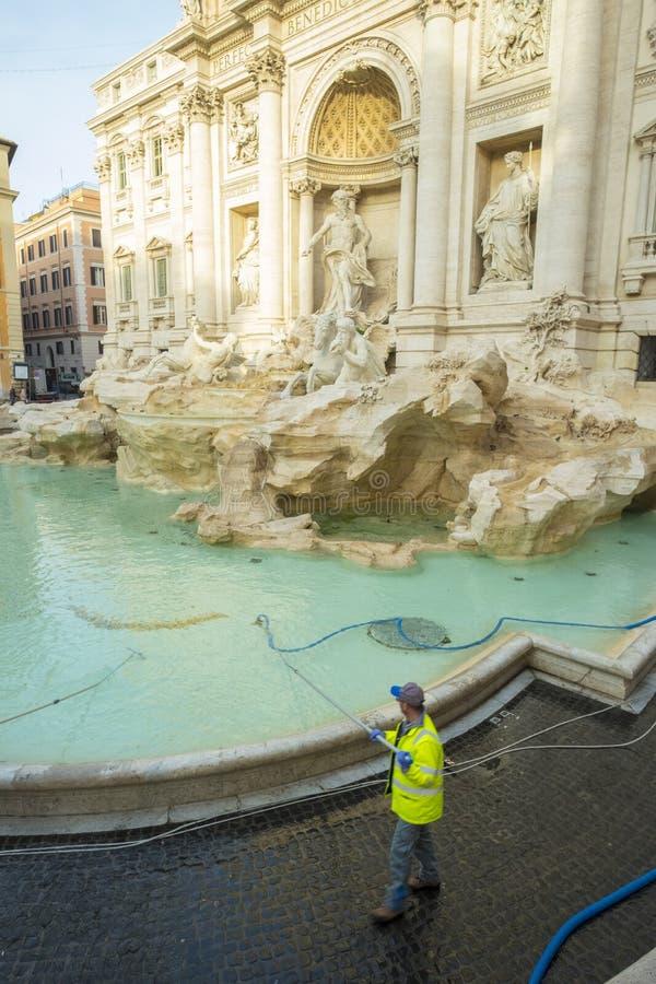 Die Reiniger, die Trevi-Brunnen staubsaugen, prägt Geld Rom lizenzfreie stockbilder