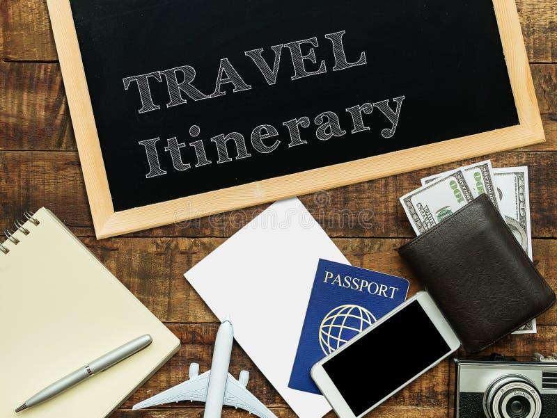 Die Reiseroute, die mit weißer Kreide auf einer Tafel handgeschrieben ist, verzieren mit flachem Modell, Pass, Geldgeldbörse, Not lizenzfreie stockbilder