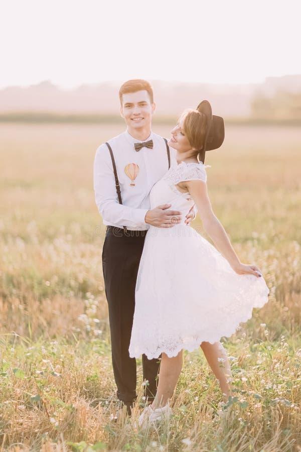Die reizende Ansicht der Jungvermähltenpaare, die auf dem Gebiet umarmen Die Braut spielt mit ihrem weißen Weinlesehochzeitskleid stockfotos