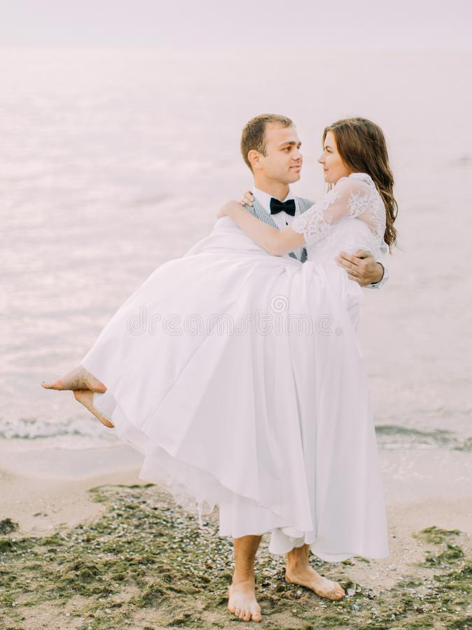 Die reizende Ansicht des Bräutigams, der die Braut in seinen Armen am Hintergrund des Meeres hält lizenzfreie stockbilder