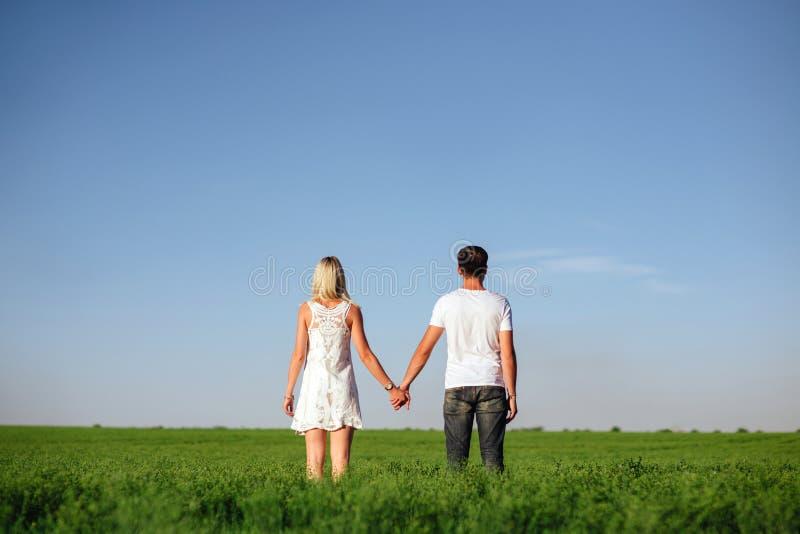 Die reizenden Paare in der Liebe auf einem Gebiet lizenzfreie stockfotografie