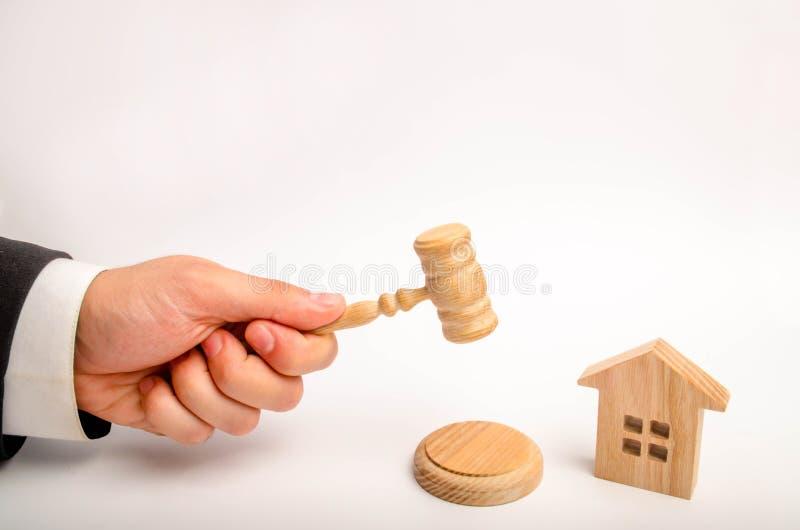 Die Richter ` s Hand hält einen Hammer nahe bei dem Holzhaus Versuch von Immobilien Beseitigung und Entfremdung des Konkurses, Co stockfotografie