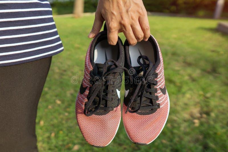 Die rosa Schuhe NIKES mit rotem Kasten Frauen für Übung am Park stockbilder