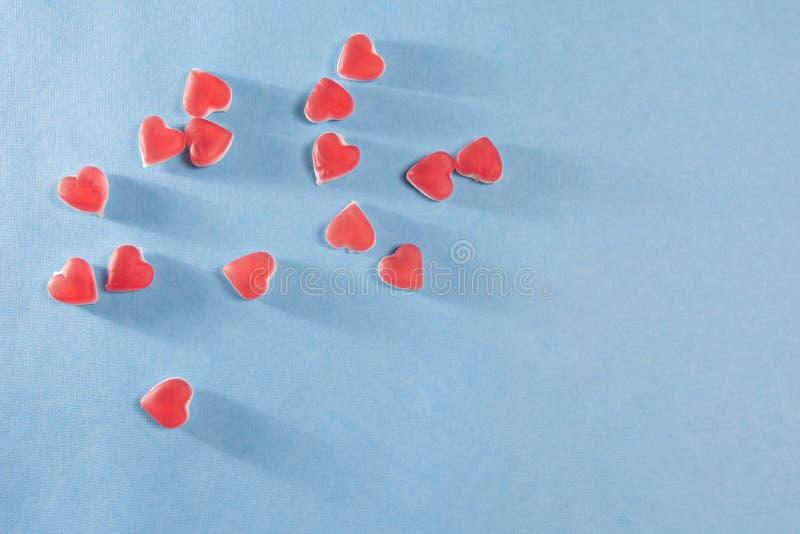 Die roten Herzen vom Kauen der Marmelade auf einem blauen Hintergrund lizenzfreies stockbild