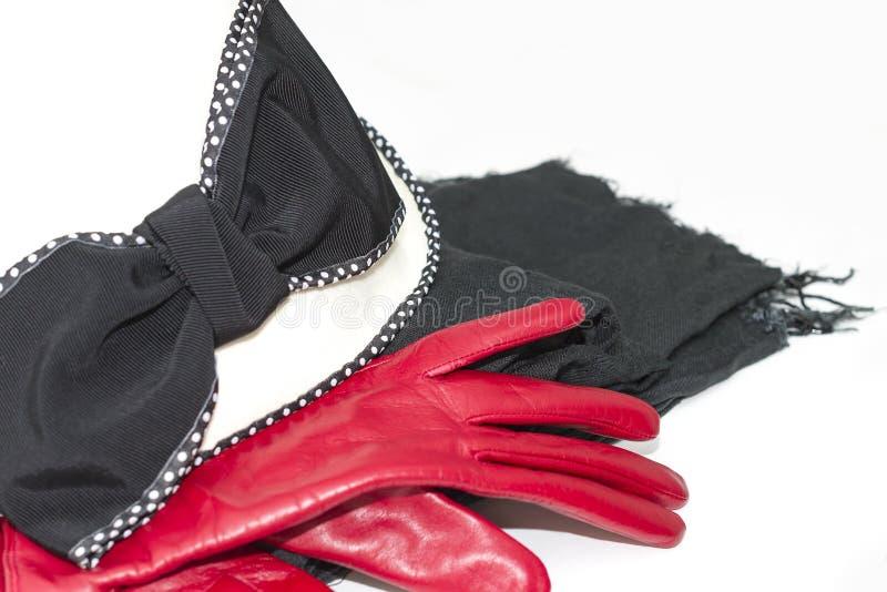 Die roten Lederhandschuhe der Frauen, weißer Hut und schwarzer Schal lizenzfreie stockbilder