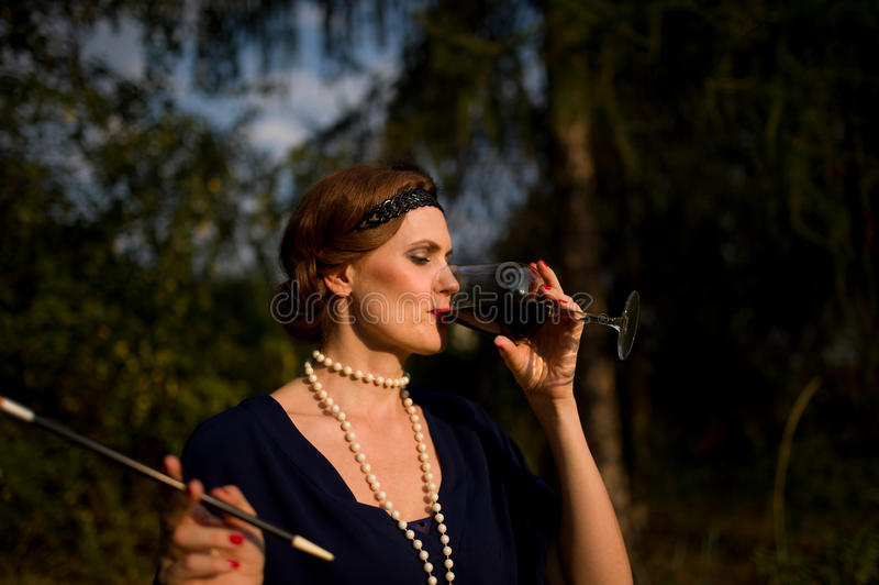 Die Rotwein-Dame im Garten - Art 1930 stockbilder