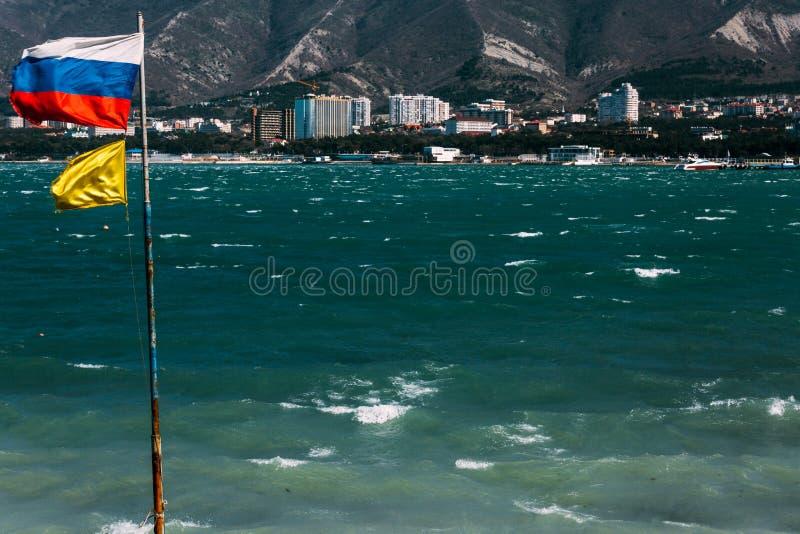 Die russische Flagge fliegt auf den Fahnenmast gegen den Hintergrund der Schwarzmeerküste von Gelendzhik-Bucht Gelendzhik, Russla lizenzfreies stockbild