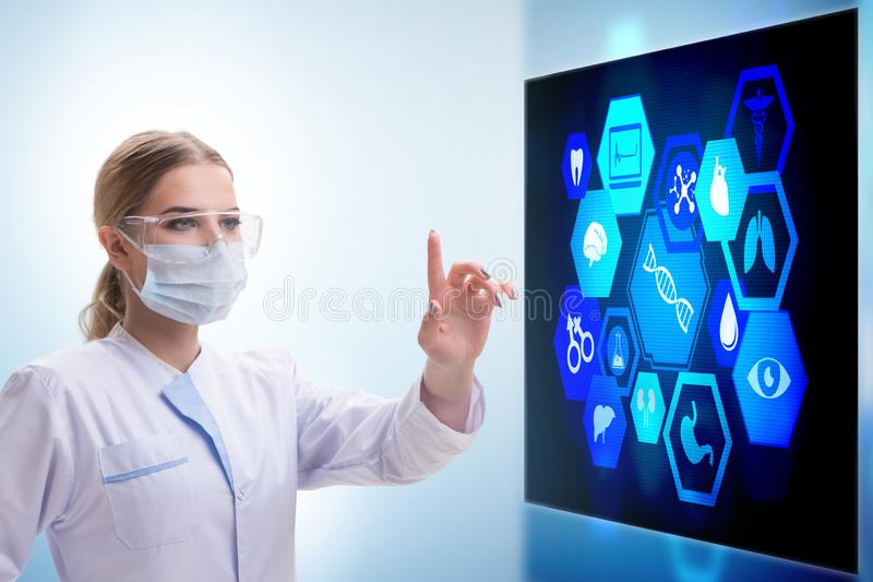 Die ?rztin im Fernmedizinkonzept, das mit Ber?hrungseingabe Bildschirm dr?ckt lizenzfreie stockbilder