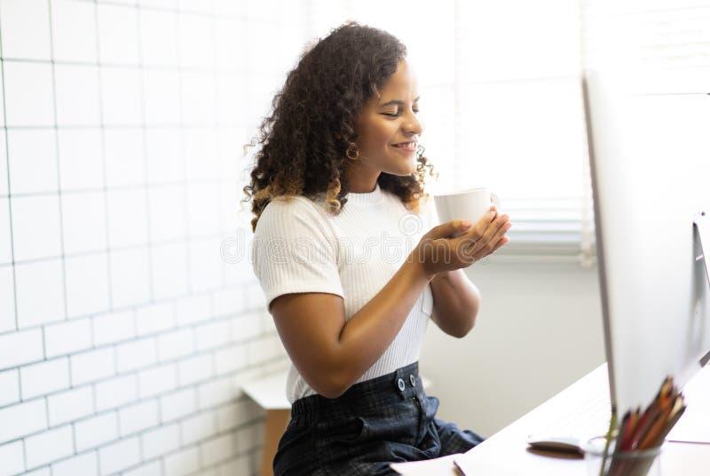 Die schöne Afrikanerin, die mit ihren Augen lächelt, schloss das Genießen des Geruchs des frischen köstlichen Kaffees beim Sitzen stockfotos