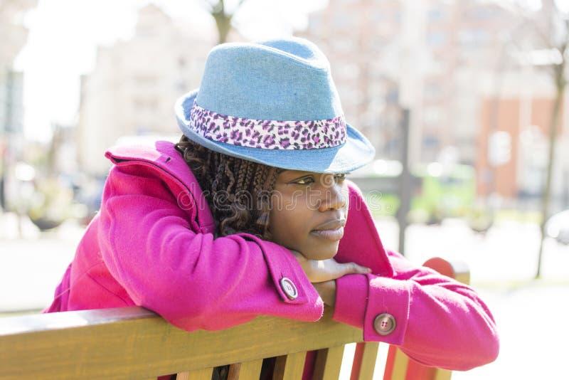 Die schöne afrikanische Frau des Porträts, die sich entspannt und meditieren, im Freien lizenzfreies stockbild