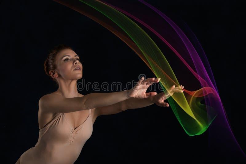 Die schöne Ballerina in einer beige Klage vom Latex tanzt auf ein d lizenzfreie stockfotos