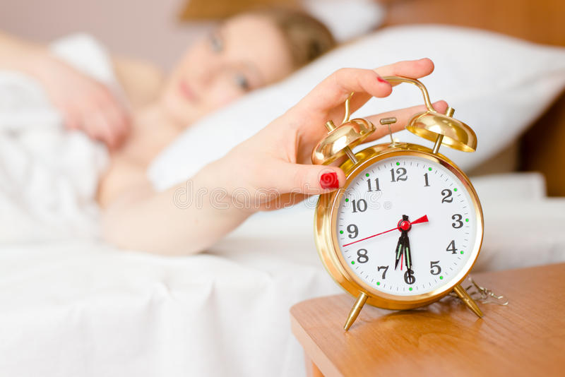 Die schöne blonde junge Frau, die Wecker wachen blockiert weg, Zeit u. das Betrachten der Uhr auf hellem Kopienraumhintergrund au stockfotografie