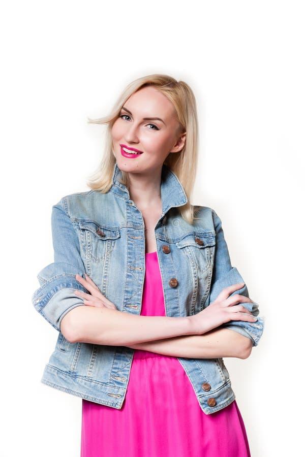 Die schöne Blondine im Studio auf einem weißen Hintergrundlächeln lizenzfreies stockfoto