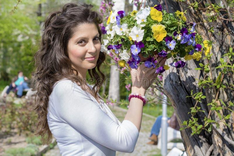 Die schöne Brunettefrau, die einen Korb des Frühlinges lächelt und hält, blüht stockfotos