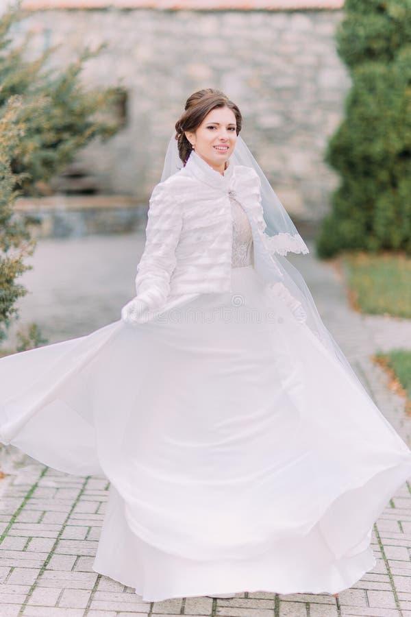 Die schöne elegante Braut, die auf grünem Park aufwirft, pflasterte die Straße, die ihr herrliches Hochzeitskleid wellenartig bew lizenzfreie stockbilder