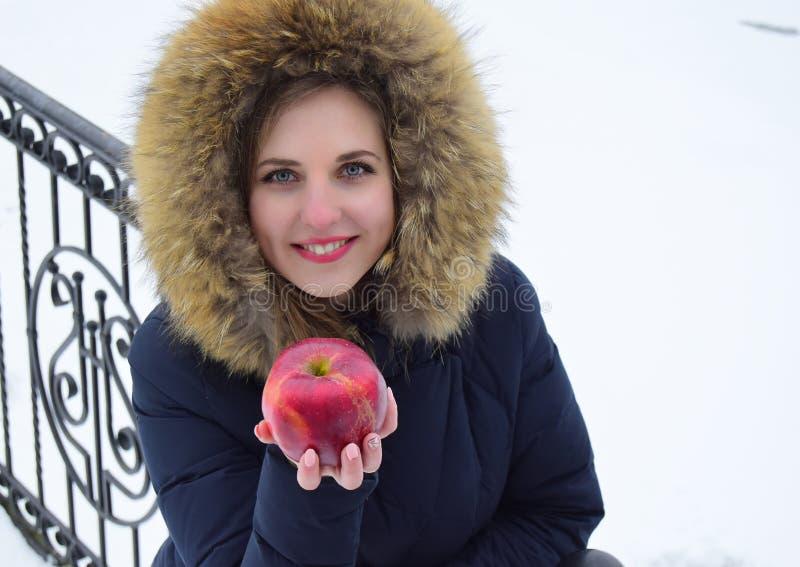 Die schöne junge Frau die Blondine mit blauen Augen hält roten Apfel in der Hand lizenzfreies stockfoto