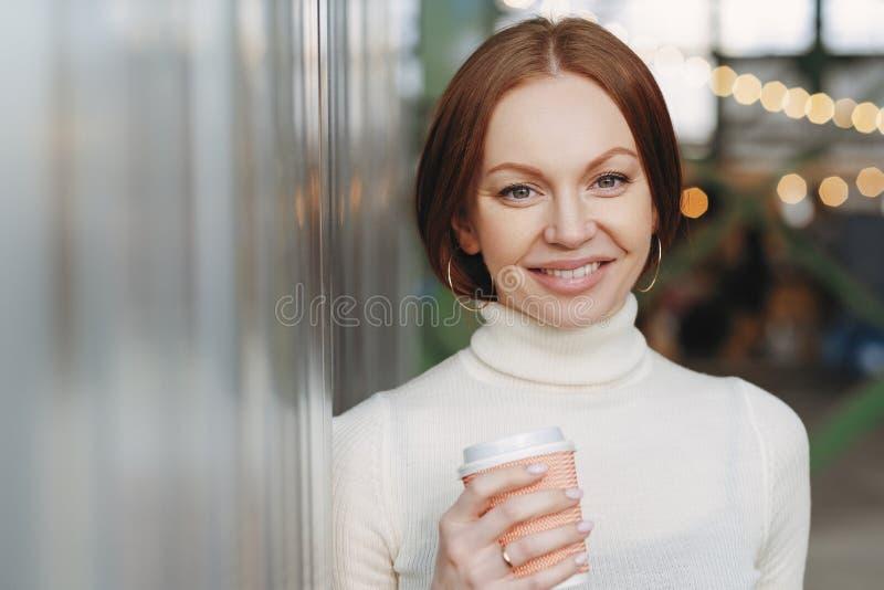 Die schöne junge Frau, die in der zufälligen weißen Rollkragenstrickjacke gekleidet wird, hält Papierschale aromatisches cappucin stockfotografie