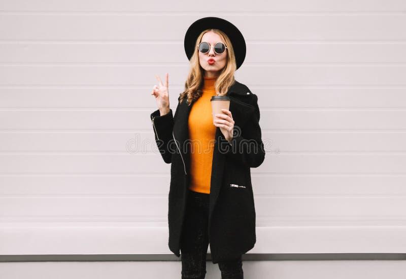 Die schöne junge Frau des Modeporträts, die rote Lippen durchbrennt, sendet einen Luftkuß, der mit Kaffeetasse in der Stadt geht stockfoto