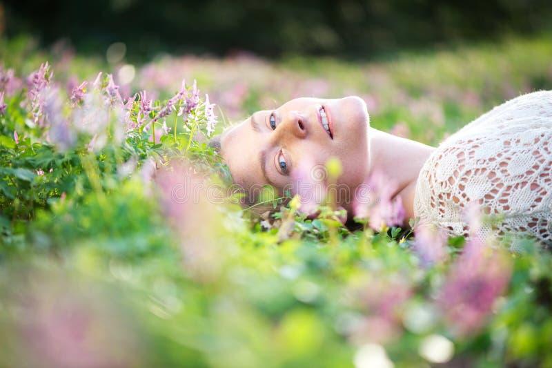 Die schöne junge Frau, die auf Gras mit Frühling liegt, blüht stockfotografie