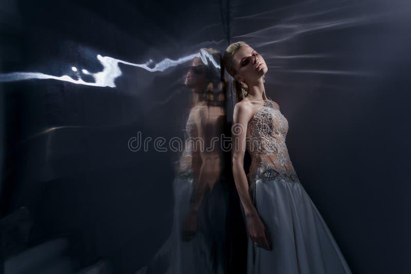 Die schöne junge Frau, die in einem Hochzeitskleid aufwirft stockbild