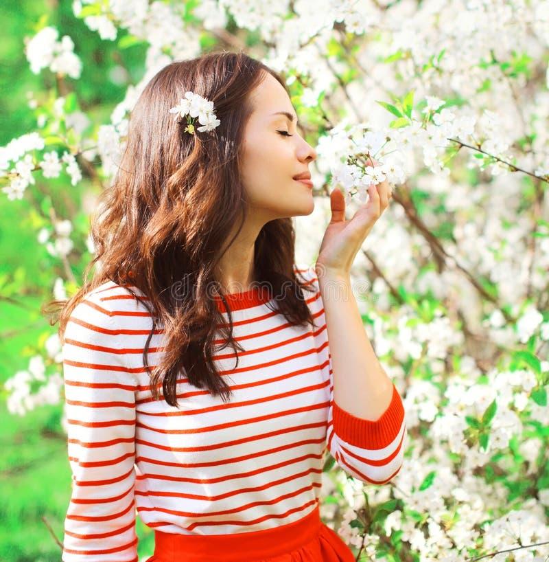 Die schöne junge Frau, die Geruchfrühling genießt, blüht im Garten lizenzfreies stockbild