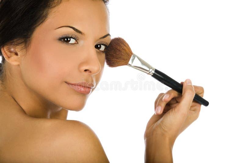 Die schöne junge Frau, die Grundlagenpulver anwendet oder, erröten mit der Make-upbürste, lokalisiert auf weißem Hintergrund lizenzfreies stockfoto