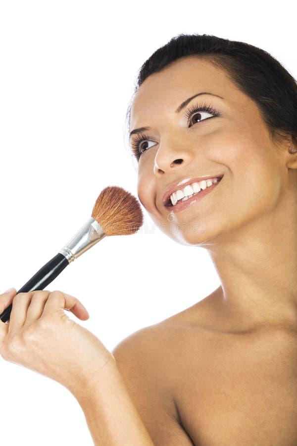 Die schöne junge Frau, die Grundlagenpulver anwendet oder, erröten mit der Make-upbürste, lokalisiert auf weißem Hintergrund stockfotos